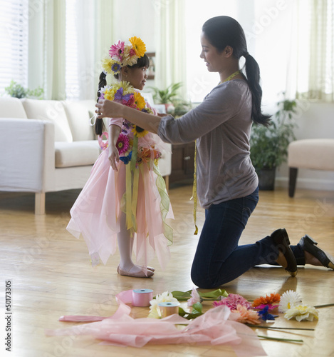 Asian woman helping daughter with costume