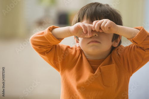 Mixed race boy covering his eyes