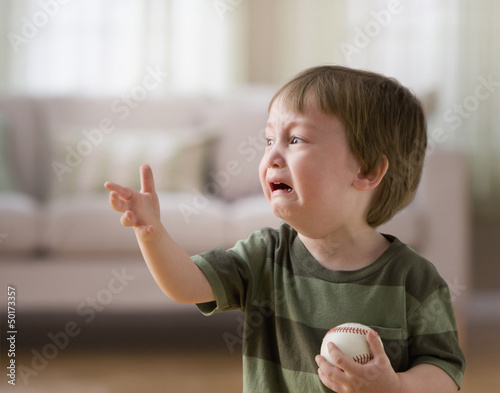 Mixed race boy crying and holding baseball