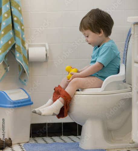 Mixed race boy using toilet