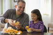 Grandfather and granddaughter peeling an orange