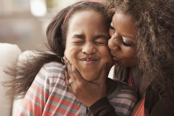 African American mother kissing daughter