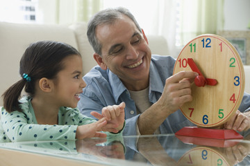 Grandfather teaching granddaughter to tell time