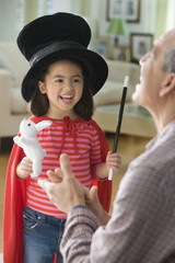 Girl performing magic for grandfather