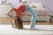 Caucasian girl doing back bend and singing into microphone