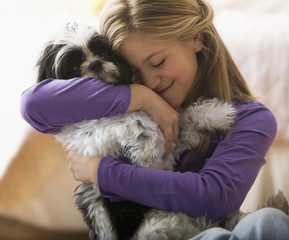 Caucasian girl hugging dog