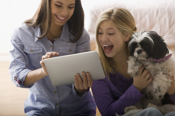 Girls sitting with dog and using digital tablet