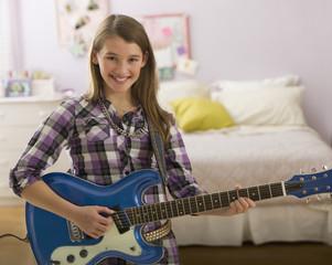 Mixed race girl playing guitar