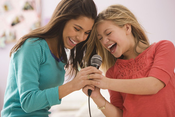 Girls singing into microphone