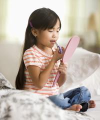 Asian girl putting on lipstick