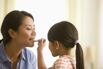 Asian girl putting on lipstick on her mother