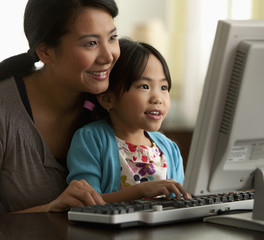 Asian mother and daughter using computer