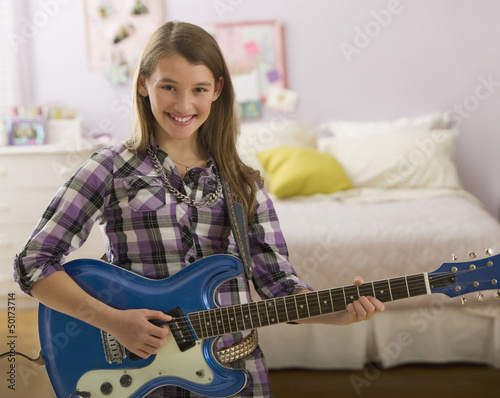 Mixed race girl playing guitar