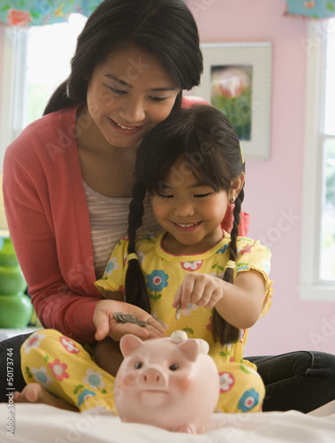 Asian mother and daughter putting coins in to piggy bank