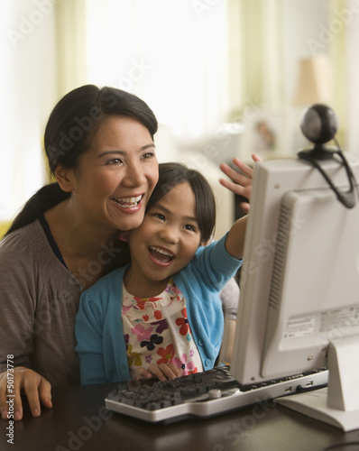 Asian mother and daughter using webcam on computer