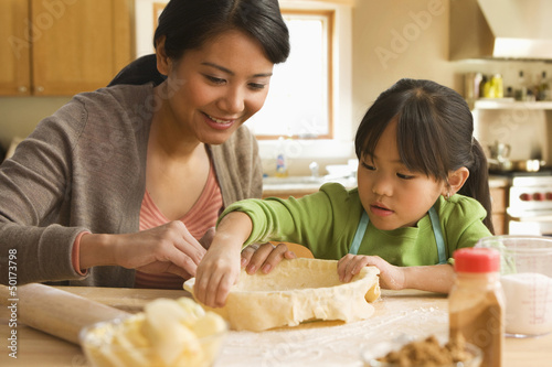 Asian mother and daughter baking pie