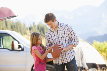 Caucasian father teaching daughter to play football