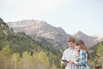 Caucasian couple looking at GPS device in remote area