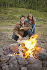 Caucasian couple enjoying campfire