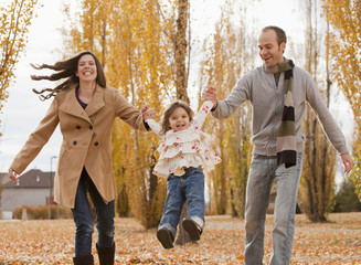 Caucasian family playing in autumn leaves