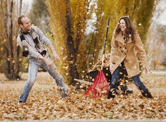 Caucasian couple raking autumn leaves