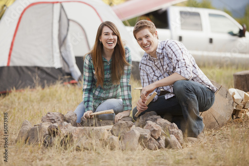 Caucasian couple building campfire at campsite