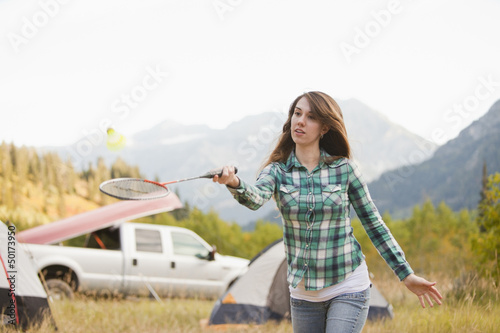 Caucasian woman playing badminton at campsite