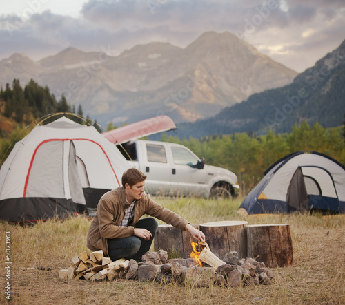 Caucasian man building campfire at campsite