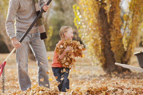 Caucasian father and daughter raking autumn leaves