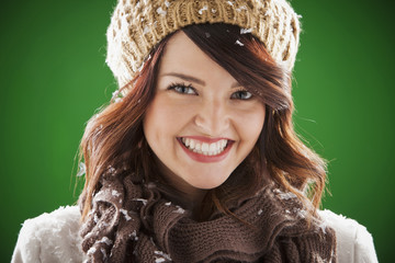 Smiling mixed race woman covered with snowflakes
