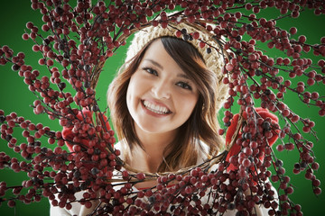 Mixed race woman holding berry wreath