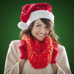 Mixed race woman wearing scarf and Santa hat
