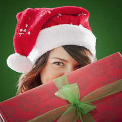 Mixed race woman in Santa hat holding Christmas gift