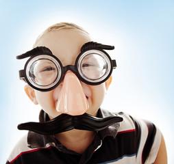 Caucasian boy in funny mustache mask
