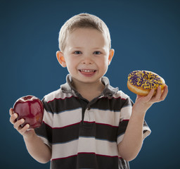 Caucasian boy holding apple and donut