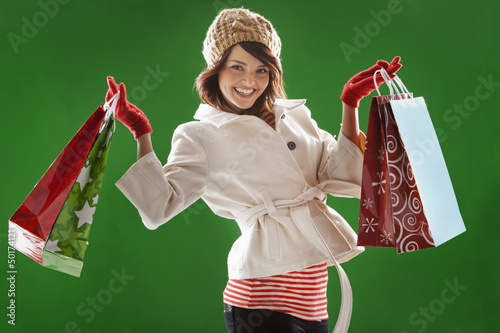Mixed race woman holding Christmas shopping bags