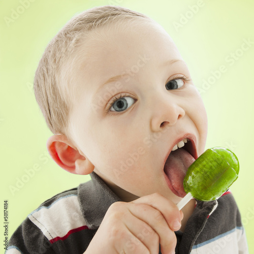 Caucasian boy licking lollipop