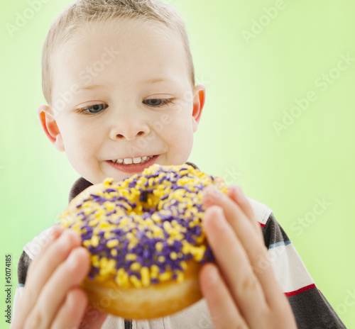 Caucasian boy eating donut