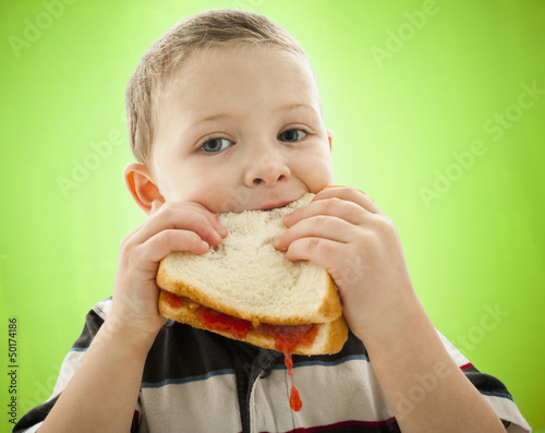 Caucasian boy eating peanut butter and jelly sandwich