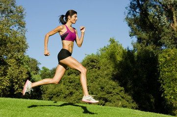 Hispanic woman running in park