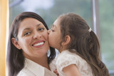 Hispanic girl kissing mother's cheek