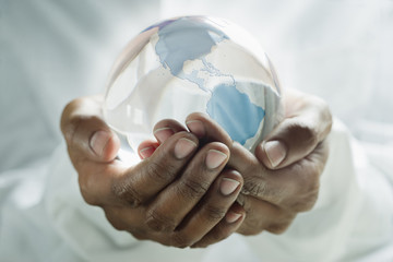 Mixed race man holding glass globe