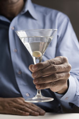 Mixed race man drinking martini