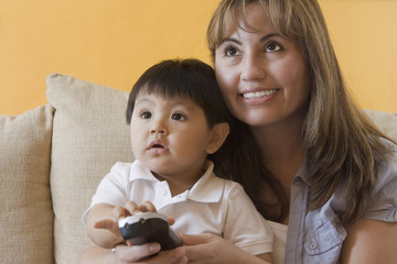 Hispanic mother and son watching television