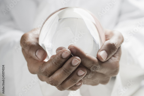 Close up of mixed race man holding crystal ball
