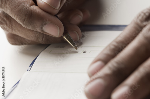 Mixed race man writing a check
