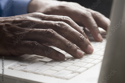 Mixed race man typing on laptop