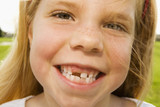 Grinning girl with tooth missing