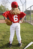 Girl in baseball uniform standing on field