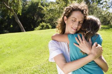 Mother hugging daughter in park